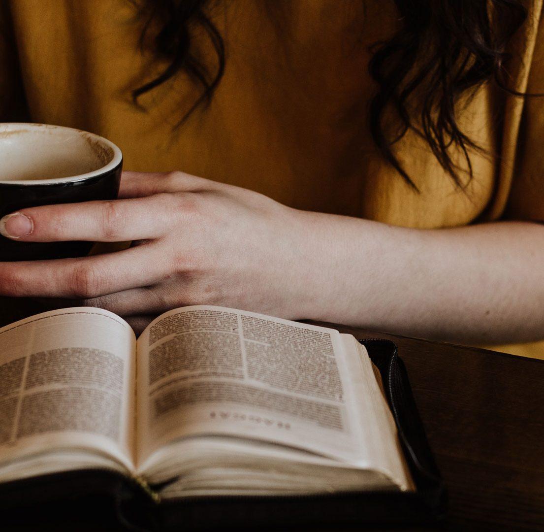 mulher lendo um livro com uma xícara de café nas mãos