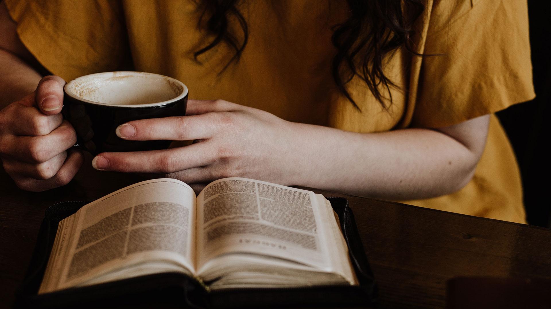 mulher desenvolvendo hábitos de leitura lendo um livro com uma xícara de café nas mãos