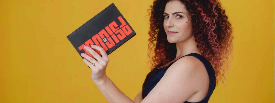 Lais Menini segura nas mãos o livro Psicose, edição Darkside Books